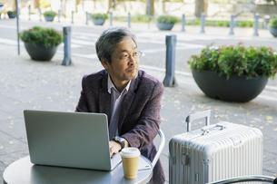 テラス席でパソコンを使う60代男性の写真素材 [FYI04483003]