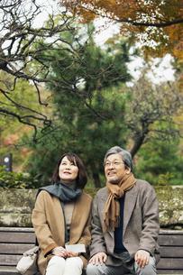 ベンチに座り話す笑顔の夫婦の写真素材 [FYI04483035]