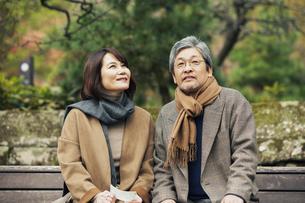ベンチに座り話す笑顔の夫婦の写真素材 [FYI04483036]