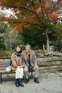 ベンチに座り風景を楽しむ笑顔の夫婦の写真素材 [FYI04483037]