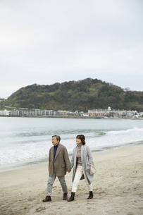 手をつなぎ浜辺を歩く男女の写真素材 [FYI04483073]