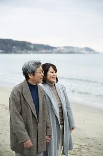 手をつなぎ浜辺を歩く男女の写真素材 [FYI04483084]