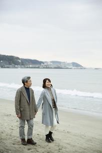 手をつなぎ浜辺を歩く男女の写真素材 [FYI04483086]