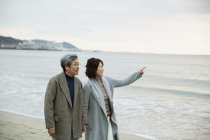 手をつなぎ浜辺を歩く男女の写真素材 [FYI04483088]