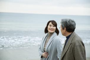 手をつなぎ浜辺を歩く男女の写真素材 [FYI04483095]