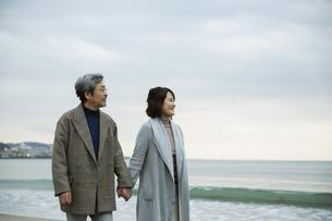 手をつなぎ浜辺を歩く男女の写真素材 [FYI04483097]