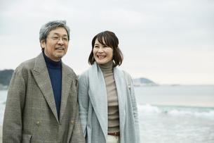 手をつなぎ浜辺を歩く男女の写真素材 [FYI04483098]