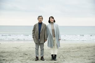 手をつなぎ浜辺に立つ男女の写真素材 [FYI04483099]