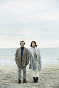 手をつなぎ浜辺に立つ男女の写真素材 [FYI04483100]