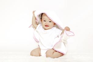 白背景の前でタオルを被り一人遊びする女の子の赤ちゃんの写真素材 [FYI04483201]