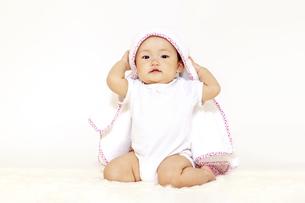 白背景の前でタオルを被り一人遊びする女の子の赤ちゃんの写真素材 [FYI04483202]