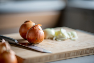 Fresh ripe onions on table in kitchen.の写真素材 [FYI04483249]