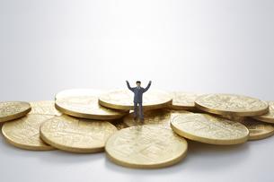 硬貨と両手をあげたミニチュアの人形の写真素材 [FYI04483338]