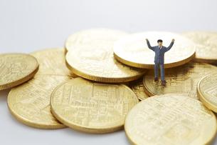 硬貨と両手をあげたミニチュアの人形の写真素材 [FYI04483340]
