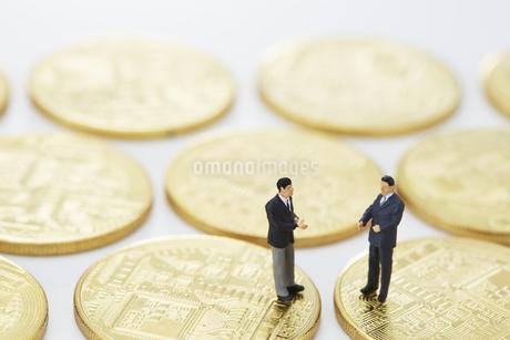 硬貨の上で会話するミニチュアの人形の写真素材 [FYI04483342]