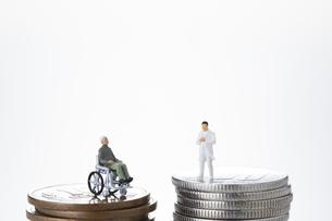 硬貨の上の年配の人と医者の人のミニチュアの人形の写真素材 [FYI04483352]