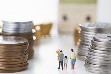 硬貨に囲まれる家族のミニチュアの人形の写真素材 [FYI04483357]