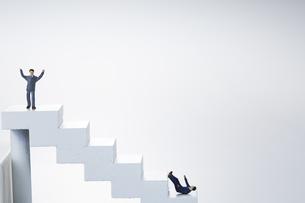 階段の頂上に立つ人と下で転ける人のミニチュアの人形の写真素材 [FYI04483363]