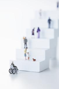 階段の下で止まる車椅子と階段を上がるその他のミニチュアの人形の写真素材 [FYI04483368]