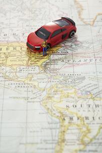 世界地図の上の赤いミニカーと男性のミニチュアの写真素材 [FYI04483385]