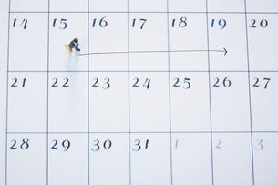 カレンダーの上を歩くサラリーマンのミニチュアの写真素材 [FYI04483387]