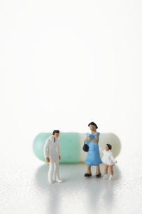 カプセル薬の前に立つ親子と医者のミニチュアの写真素材 [FYI04483394]
