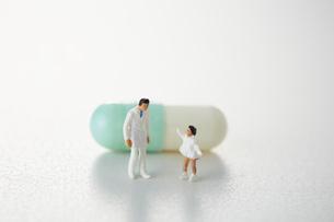 カプセル薬の前に立つ医者と少女の写真素材 [FYI04483395]