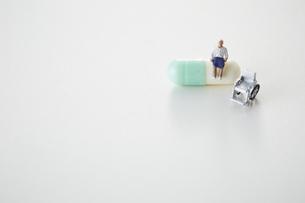 カプセル薬の上に座る老人と車椅子の写真素材 [FYI04483402]