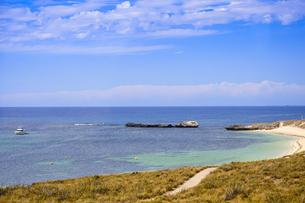 オーストラリア・西オーストラリア州のフリーマントルの沖合約18kmのインド洋に浮かぶロットネスト島の草が茂る岸辺と白い雲と白い船の景観の写真素材 [FYI04483424]