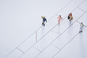 あみだくじの線上を歩き進む4人の違った人々の写真素材 [FYI04483432]