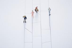 あみだくじの線上を歩き進む4人の違った人々の写真素材 [FYI04483433]