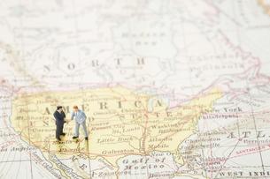 世界地図の上に立って握手を交わすビジネスマン達の写真素材 [FYI04483441]