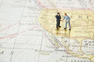 世界地図の上に立って握手を交わすビジネスマン達の写真素材 [FYI04483443]