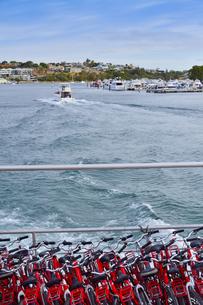 オーストラリア・西オーストラリア州のインド洋を走るフェリーに積まれた沢山の自転車と建物と船のある光景の写真素材 [FYI04483464]