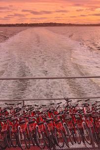 オーストラリア・西オーストラリア州の夕焼けの海のフェリーに詰め込まれた沢山の自転車と波の光景の写真素材 [FYI04483538]