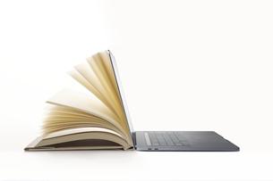 パソコンと一体化するページがめくられる本の写真素材 [FYI04484128]
