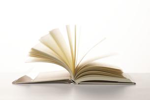 白場に広げられページがめくられる1冊の本の写真素材 [FYI04484129]