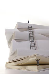 本の頂上と本の下でページを持ち上げるミニチュアの写真素材 [FYI04484133]