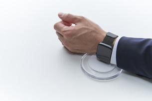 スマートウォッチを決済用端末にかざすスーツを着た男性の写真素材 [FYI04484143]