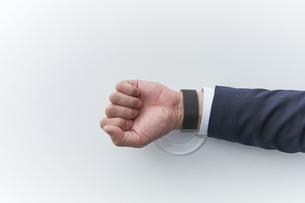 スマートウォッチを決済用端末にかざすスーツを着た男性の写真素材 [FYI04484144]