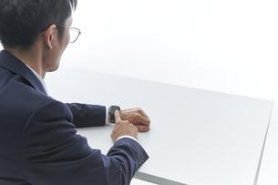 スマートウォッチを操作しているスーツ姿の男性の写真素材 [FYI04484147]