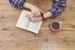 スマートウォッチをした読書をする女性の写真素材 [FYI04484149]
