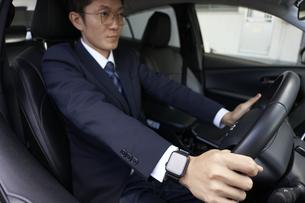 スマートウォッチをしてハンドルを握るスーツを着た男性の写真素材 [FYI04484153]
