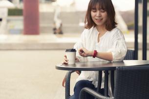 お茶をしながらスマートウォッチを確認している女性の写真素材 [FYI04484160]