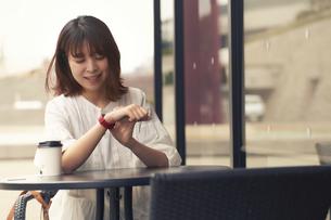 お茶をしながらスマートウォッチを確認している女性の写真素材 [FYI04484161]
