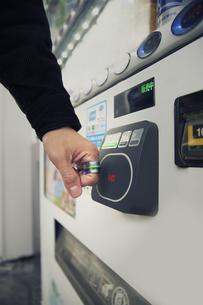 スマートリングを自動販売機のカードリーダーにかざす男性の手元の写真素材 [FYI04484168]