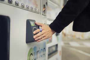 スマートリングを自動販売機のカードリーダーにかざす男性の手元の写真素材 [FYI04484169]