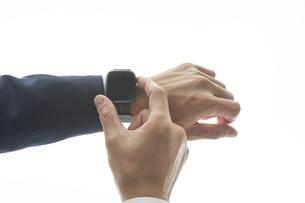 スマートウォッチを操作するサラリーマンの手元の写真素材 [FYI04484184]