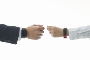 スマートウォッチをかざし合う男性と女性の手元の写真素材 [FYI04484186]