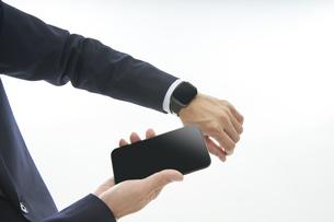 スマートウォッチとスマートフォンを持つサラリーマンの手元の写真素材 [FYI04484196]